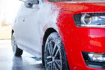 Car cleaning. Wash red car with soap. High pressure water washing