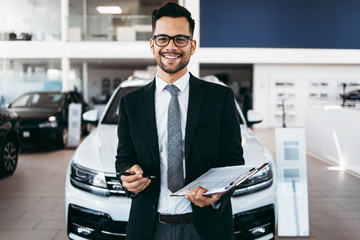 Good looking, cheerful and friendly salesman poses in a car salon or showroom.