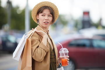 Pensive stylish girl in summer hat carrying shopping bags on shoulder and drinking summer beverage while walking over car park