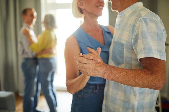 Mid-section portrait of unrecognizable senior couple dancing romantically holding hands, copy space