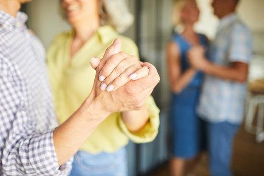 Closeup of unrecognizable senior couple dancing romantically holding hands, copy space