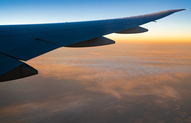 Wing of plane over white clouds. Airplane flying on sunrise sky. Scenic view from airplane window. Commercial airline flight. Plane wing above clouds. Flight mechanics concept. International flight.