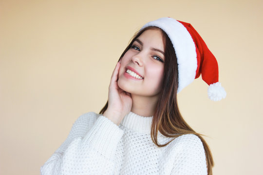 Beautiful smiling girl with clean skin in santa hat an cozy white sweater on beige background