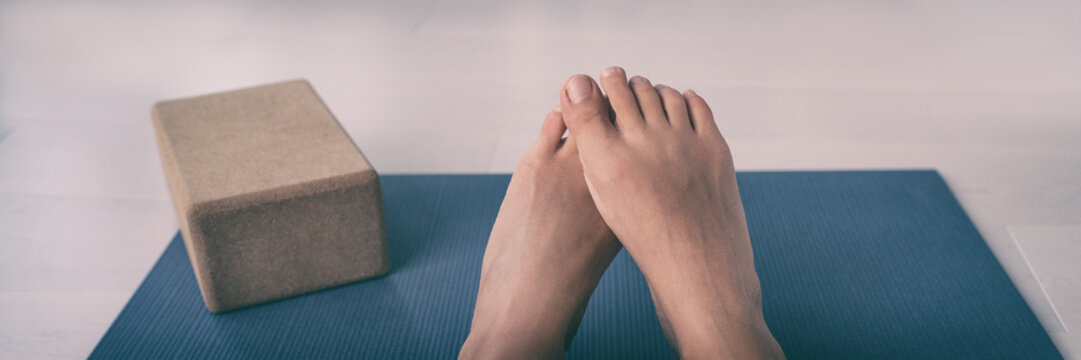 Barefoot yoga class woman shy feet lying on exercise mat at fitness studio room panoramic banner. Healthy sport lifestyle. Foot care or embarrassment of stinky bare feet.