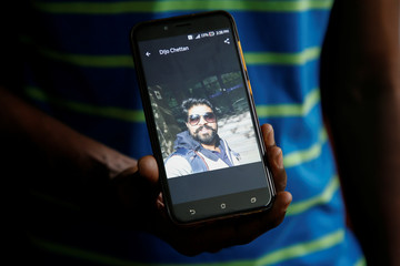 A relative shows photographs of Dijo Pappachan, one of the crew members of British-flagged vessel owned by Stena Bulk, seized by Iran, in Kochi
