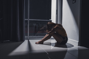 Depressed young woman sitting alone on the floor in the living room. Major depressive disorder concept. Selective focus