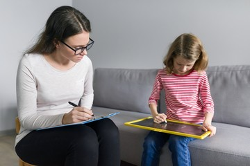 Professional child psychologist talking with child girl in office