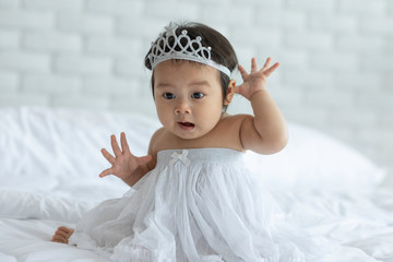 Cute Sweet Adorable Asian Baby wearing bride dress and diadem Sitting on white bed smiling and playing with happiness emotional in cozy bedroom,Healthy Baby Concept