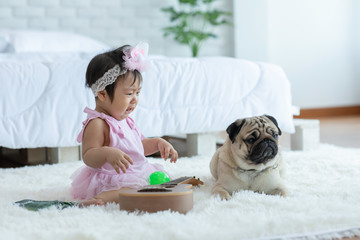 Cute Sweet Adorable Asian Baby wearing pink dress Sitting on white carpet Crying with dog pug breed Friendly in cozy bedroom,Dog with Baby Concept