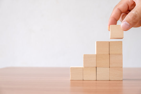 Business concept of ladder career path and growth success process. Hands of men arranging wood cube block stacking for top staircase shape on wooden table.