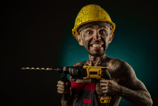 A man miner in a worker s clothes and a helmet, dirty, in soot, with a naked body, grimaces at the camera