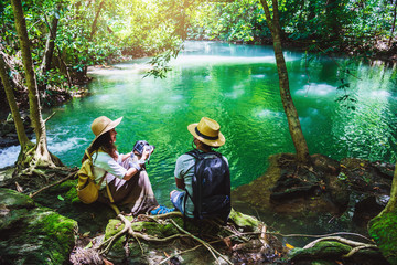 Travel couples with backpacks sitting and relax on the rocks. travel nature in greens jungle and enjoying view in waterfall. Tourism, hiking, nature study. Couples traveling taking pictures of nature
