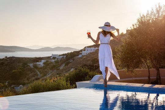 Elegante Frau in weißem Sommerkleid steht am Pool und genießt den Sonnenuntergang mit einem Cocktail in der Hand