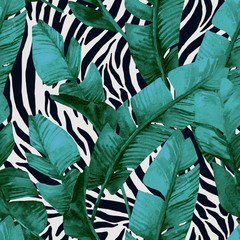 Banana leaf on animal print seamless pattern. Unusual tropical leaves, tiger stripes background