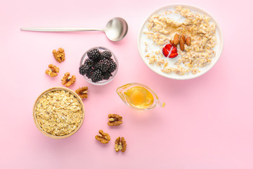 Tasty sweet oatmeal in bowl with nut, berries and honey on color background