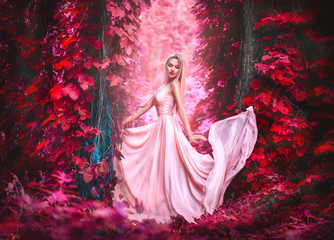 Beauty romantic young woman in long chiffon dress with gown posing in fantasy misty forest. Beautiful happy bride model girl enjoying nature outdoors
