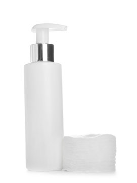 Bottle of cosmetic product and pads for makeup removal on white background
