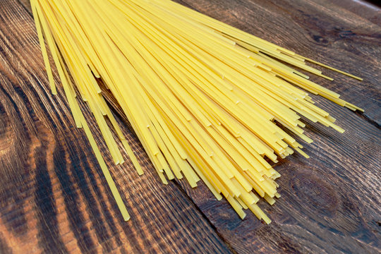 spaghetti, macaroni, pasta, linguine durum wheat Italian thin long on wooden background close up selective focus