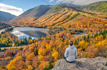 Woman hiking at Artist's Bluff in autumn. View of Echo Lake. Fall colours in Franconia Notch State...