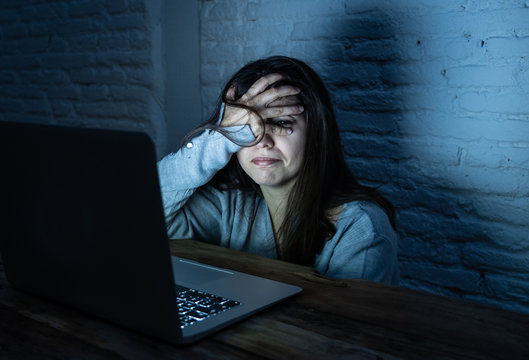 Scared woman on laptop in the dark feeling fear suffering online harassment and cyberbullying