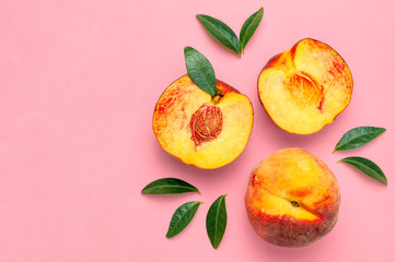 Flat lay composition with peaches. Ripe juicy peaches with green leaves on pink background. Flat lay, top view, copy space. Fresh organic fruit, vegan food. Harvest concept.