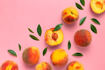 Wall Mural - Flat lay composition with peaches. Ripe juicy peaches with green leaves on pink background. Flat lay, top view, copy space. Fresh organic fruit, vegan food. Harvest concept.