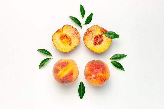 Flat lay composition with peaches. Ripe juicy peaches with green leaves on white background. Flat lay, top view, copy space. Fresh organic fruit, vegan food. Harvest concept