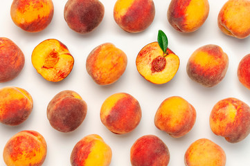 Wall Mural - Flat lay composition with peaches. Ripe juicy peaches with green leaves on white background. Flat lay, top view, copy space. Creative peaches pattern. Fresh organic food. Harvest concept