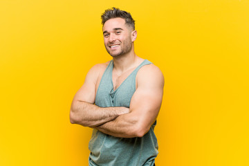 Young fitness man against a yellow background smiling confident with crossed arms.