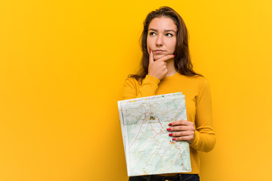 Young european woman holding a map looking sideways with doubtful and skeptical expression.