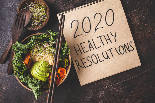 2020 new year, healthy resolutions. Buddha bowl on a dark background.