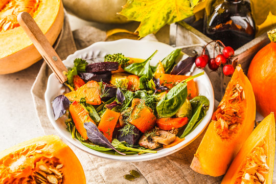Autumn salad with baked pumpkin, beet, zucchini and carrots. Healthy vegan food concept.