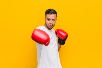 young filipino man boxing with red gloves