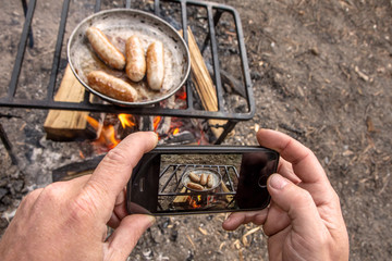 Man takes pictures on phone grilled sausages on pan grill with smoke and flame on a meadow.