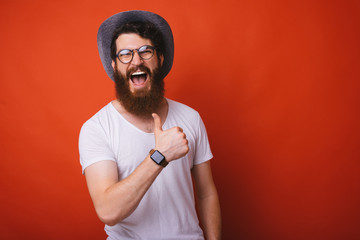 Photo of excited bearded guy in hat and glasses, showing thumb up over red backgroung