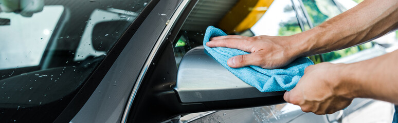 panoramic shot of man cleaning wet car mirror with blue rag
