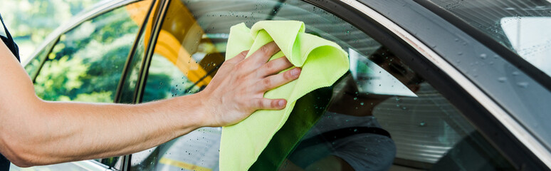panoramic shot of car washer holding green rag and cleaning car window