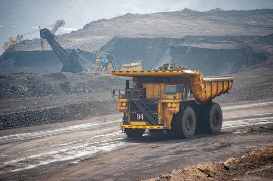 Big yellow mining truck hauling rock in dusty coal mine