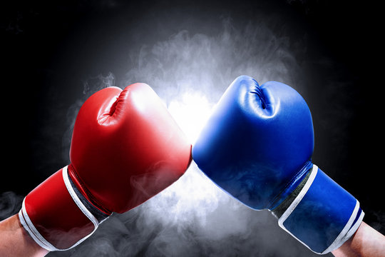 Hands of two men with blue and red boxing gloves