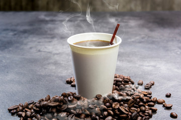 Styrofoam cup with hot coffee and coffee beans