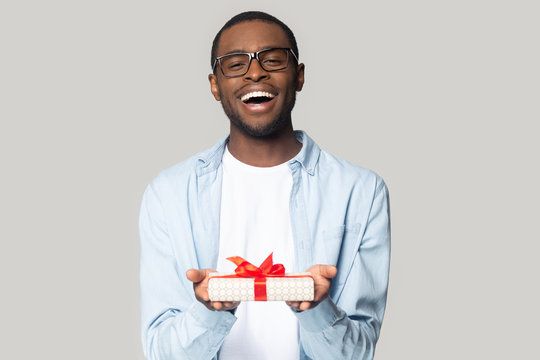 Happy african American man present gift box with bow
