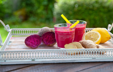Beetroot ginger and lemon smoothie on garden green Background