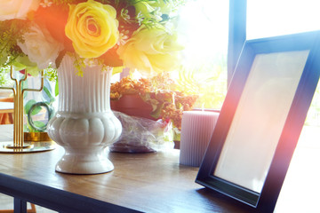 Empty photo frame on wood table decorated by flowers in vase