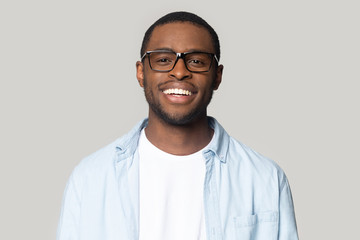 Portrait of smiling black man in glasses isolated in studio