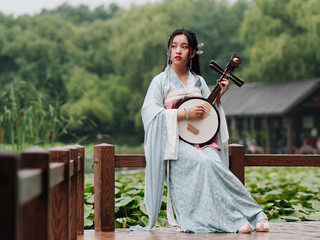 Beautiful Asian woman in cyan costume clothes hanfu holding yueqin (four stringed plucked instrument) with lotus pond background in rainy day, traditional ancient Chinese beauty, time travel fiction.