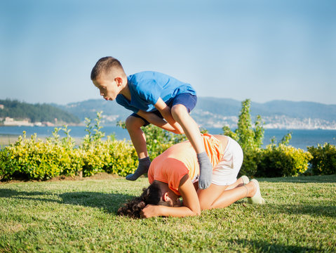 children playing leapfrog in the grass