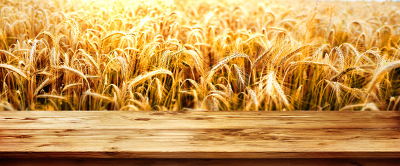 Golden wheat field with wooden table Fotoväggar