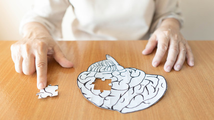 Elderly woman hands putting missing white jigsaw puzzle piece down into the place as a human brain shape. Creative idea for memory loss, dementia, Alzheimer's disease and mental health concept. Wall mural
