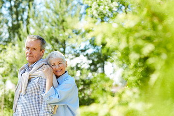 Portrait of happy senior woman leaning on her husband while taking family portrait outdoors, copy space