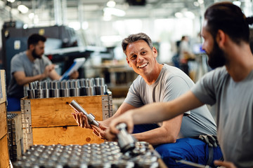 Happy manual workers talking while working together at steel factory. Wall mural